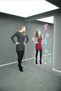 young girl shopping using augmented reality mirror with alternate fashion being shown