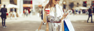 Cheerful woman is shopping in the city. She is holding a coffee to go and using her smart phone.